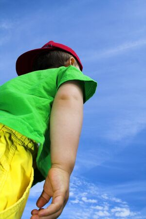 child standing outside over deep blue sky photo