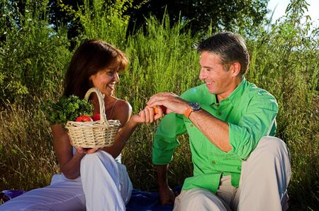 couple having a pic nic outdoor at sunset photo