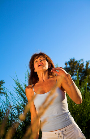 woman sneezing outdoor on a field over blue sky 스톡 콘텐츠