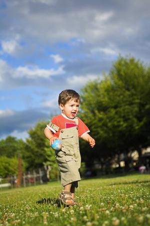 ni�o peque�o corriendo en un campo durante el d�a  Foto de archivo - 1543651