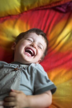 close up laughing on red and yellow bed