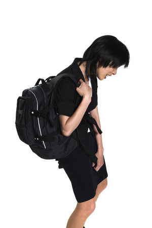 back ache: young woman carrying back-pack over white background