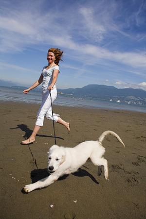 woman running with her dog on the beach
