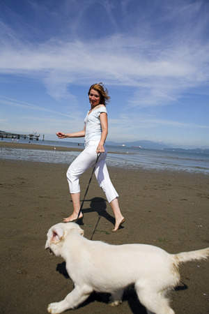 woman running with her dog on the beach photo