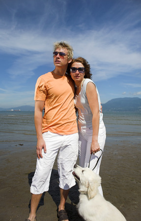 young couple on the beach with dog in vancouver photo