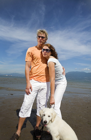 young couple on the beach with dog in vancouver Stock Photo - 1575636