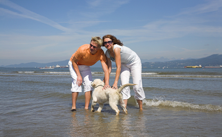 young couple petting dog on the beach vancouver photo