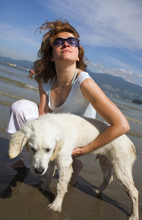 woman portrait petting her dog on the beach photo