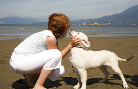 woman giving a kiss to her dog on the beach Stock Photo - 1575632
