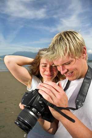 young couple on the beach taking pictures photo