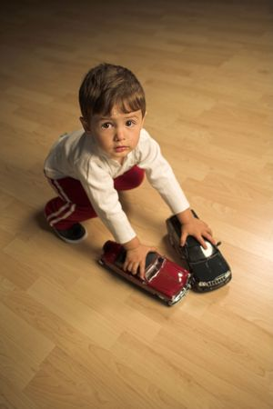 little boy playing indoor with model cars