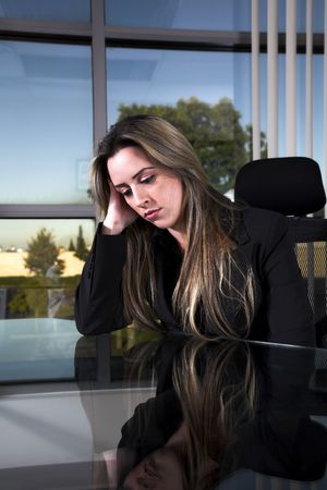 business woman indoor shot sitting depressed at her desk photo