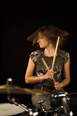 shot of woman drummer playing over black backdrop Фото со стока