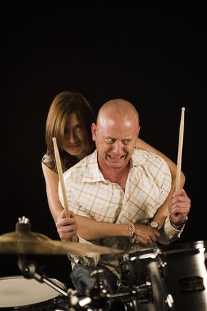 bugging: shot of woman bugging drummer playing over black backdrop