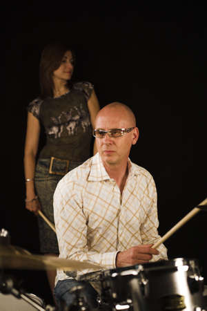 drummer playing over black backdrop with woman standing in background Фото со стока