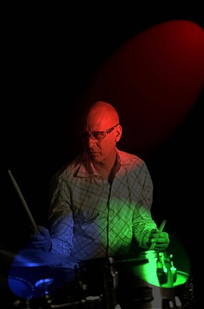 drumset: drummer playing over black backdrop with rgb lighting