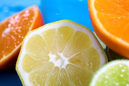 oranges and lemons in transparent glass over blue background Stock Photo