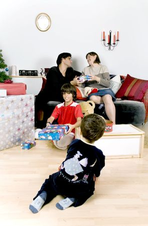 new age: happy family having fun and opening gift at christmas time