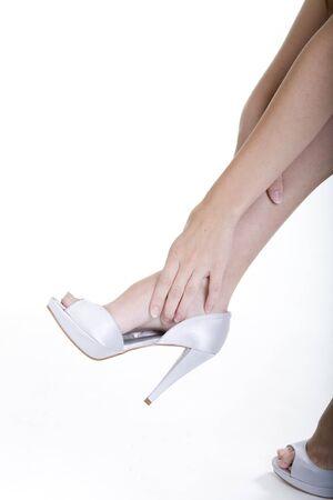 overwhite: woman rubbing her legs over white background Stock Photo