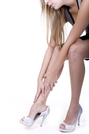 fem: woman rubbing her legs over white background Stock Photo