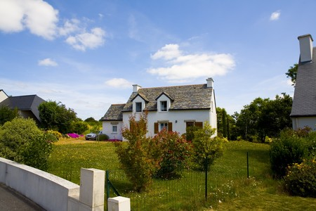house in brittany with flowers and grass over blue sky photo