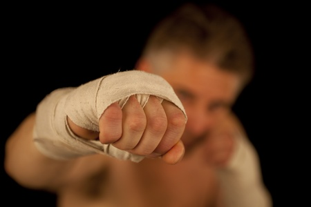 man boxing posing over black background