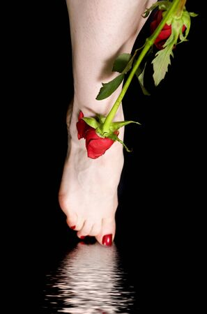 green background: female feet with a rose over black background