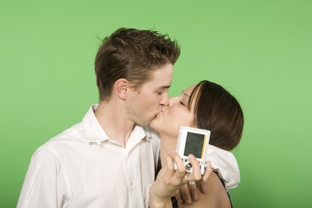 couple kissing holding digital camera over green screen photo