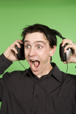 man listening to unplaisant music over black background photo