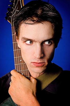 man close up: uomo vicino ritratto con la chitarra su sfondo blu Archivio Fotografico