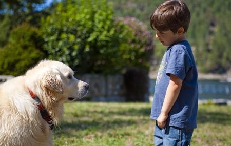 boy looking at dog at day time photo