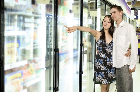 youg couple looking at food near freezer in grocery store Zdjęcie Seryjne