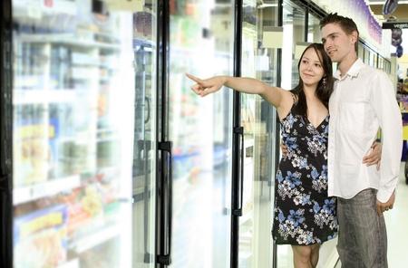 youg paar op zoek naar voedsel in de buurt vriezer in supermarkt Stockfoto