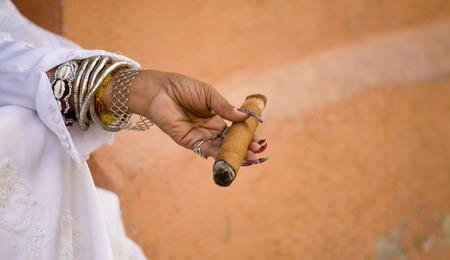 womans hand holding a cigar over orange wall photo