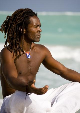 yoga pants: yoga black man on the beach over blue sea and grey sky