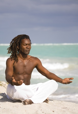 yoga black man on the beach over blue sea and grey sky