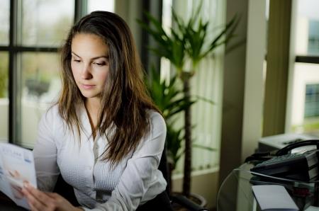 werk: vrouw, zittend achter een bureau het dragen van witte shirt in een kantoor