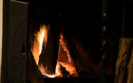 snuggle: Fireplace inside home burning wood. For heating and recreational use, or simply romantic snuggle time Stock Photo