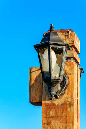 outdoor lighting: Wooden light pole with broken glass on the pier from Armao Beach in Buzios