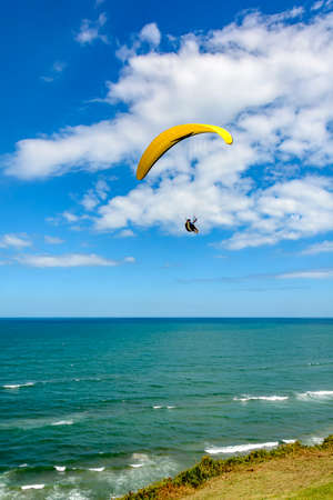 cal: Paragliding flight on the Lighthouse hill on the beach Cal in the city of Torres, Rio Grande do Sul Stock Photo