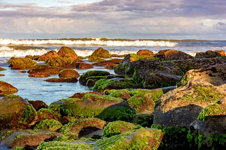 bordering: Meeting between the rocks and the sea in Cal beach. Torres city, Rio Grande do Sul, bordering Santa Catarina Stock Photo