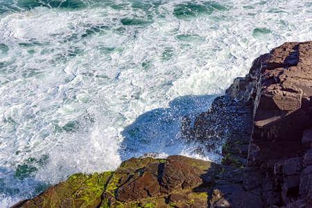 heavily: Waves crashing heavily against the rocks Stock Photo