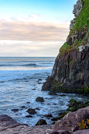 Stone wall ending in the sea where it meets the sea and the waves Stock Photo
