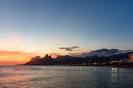 seafronts: Landscape of the beaches of Arpoador, Ipanema and Leblon in Rio de Janeiro During dusk with its lights, moon and sky and the hill Two brothers and G�vea stone in the background