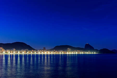 Copacabana Beach and Sugar Loaf seen at night with its buildings, lights, sea, hills and contours