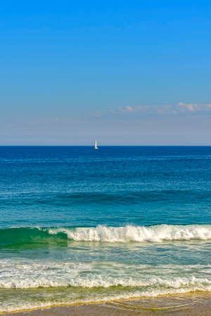 cruising: Sailboat sailing at horizon line of the blue waters of Ipanema beach at Rio de Janeiro