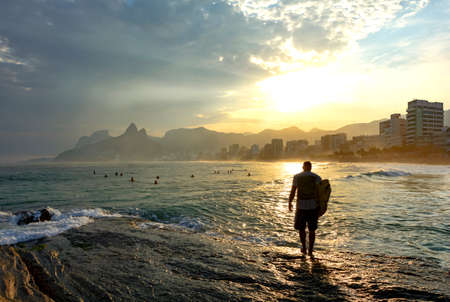 Surf at sunset over the rocks in Arpoador beach at Ipanema in Rio de Janeiro