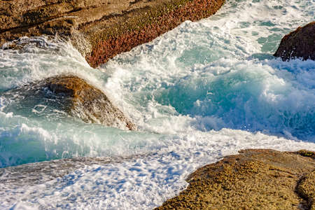oceanic: Sea water splashing over the stones on the beach