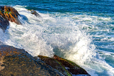 Sea water spray over the stones on the beach