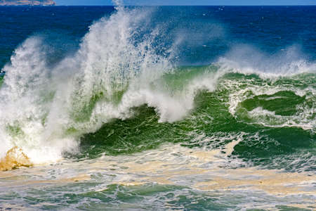 breaking: Big, dangerous waves during tropical storm in the green and blue waters of Rio de Janeiro, Brazil